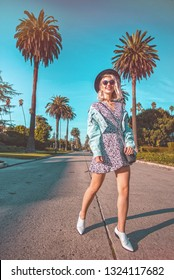 California girl walking down the street surrounded by palm trees