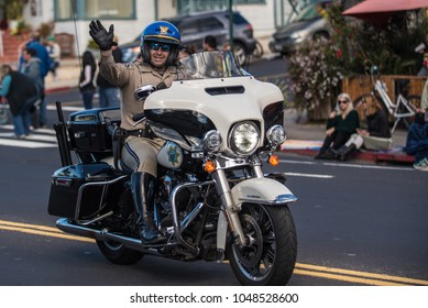 California Highway Patrol officer on motorcycle waves to crowd during annual Saint Patrick's Day Parade in Ventura, California on March 17, 2018 in United States.