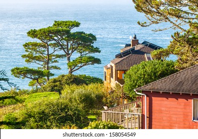 California houses on a hillside with views of the Pacific Ocean. One has solar panels installed on the roof. Location: Muir Beach, near San Francisco.