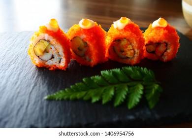 California maki sushi roll on black plate
