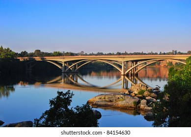 California morning sunrise. American river bridge near old Folsom city calm blue water reflect clear sky