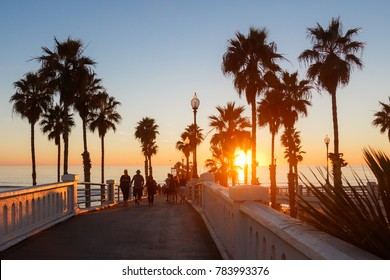 California Oceanside pier over the ocean at sunset with beach and surfers