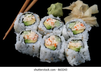A california roll sushi isolated on black background, with chopsticks and wasabi