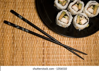 California rolls on black plate with copsticks.