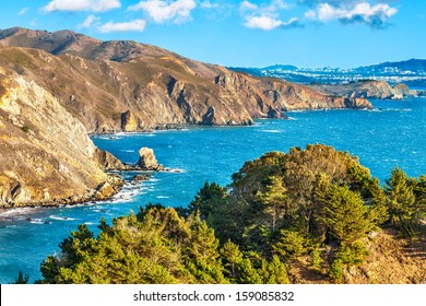 California scenic coastal cliffs along the Pacific Ocean with the city of San Francisco in the background. Blue sky with drifting clouds.