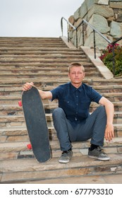 California skateboarder seated on slate stairs holding board with hand.