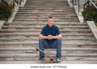 California skateboarder seated on slate stairs holding board with foot.