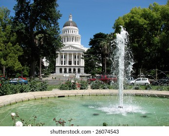 California State Capital in Sacramento on a perfect day with green trees and blue sky framing the white building through a fountain