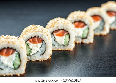 California Sushi maki with salmon and philadelphia cheese on the dark background , focus on one roll