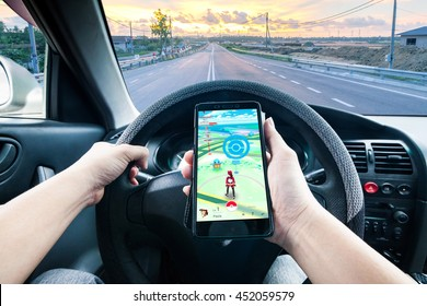 California, United State, July 2016 : Hand holding a cellphone playing Pokemon Go game while driving indicating dangerous