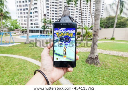 California, United States, July 2016 : Left hand holding a cellphone to play Pokemon Go with blur background