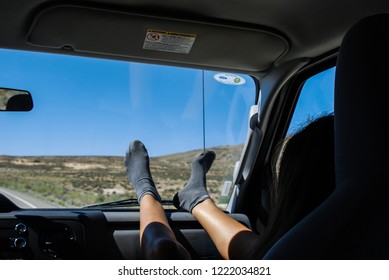 California - USA - 08-09-2010: girl sitting in a very dangerous way in case of car crash.  Feet on the dashboard.