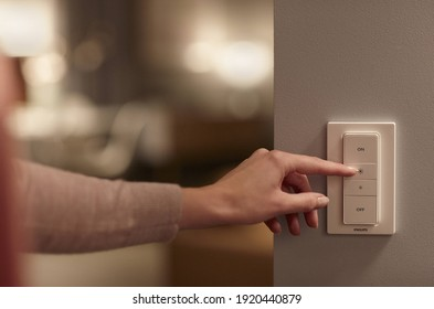 California, USA - August 17 2020: A white philips smart switch on a white wall with a white woman's hand