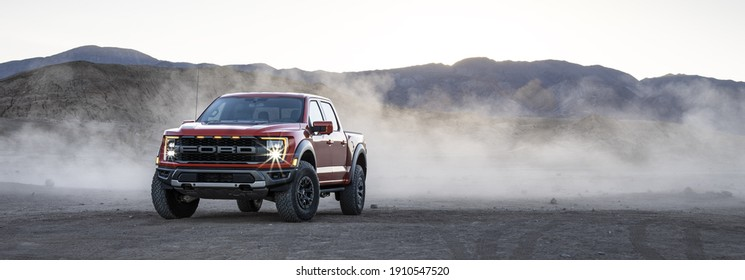 California, USA - January 10, 2021: A red Ford F-150 Raptor is driven in desert