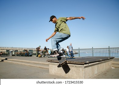 California, USA - October 20th, 2019 : Skateboarders grinding on a pole on the boardwalk.