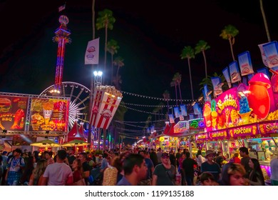 California, USA - September 23rd, 2018. Many people come to LA County fair that takes place in Pomona, CA. The street is filled with crowd of people who are enjoying, walking and eating on night .