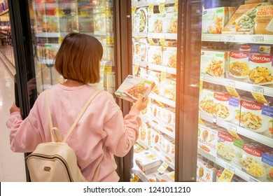 California, USA - September 30, 2018 : A girl takes frozen foods from the supermarket's refrigerator. The girl chooses goods in the store. Shopping in the supermarket.
