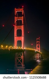 California's Golden Gate Bridge, suspended in the night from two massive art deco style towers, crosses the opening of the San Francisco Bay to the Pacific Ocean.