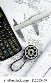caliper, blueprint and calculator