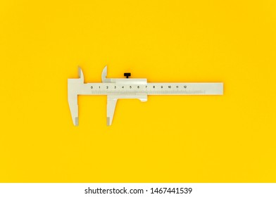caliper close-up view from above on a yellow background, a working tool for accurately measuring the diameter of pipes and other round objects.