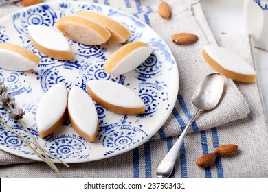 Calissons d'Aix-en-Provence on a ceramic plate on a white wooden background. Traditional French Provence sweets.