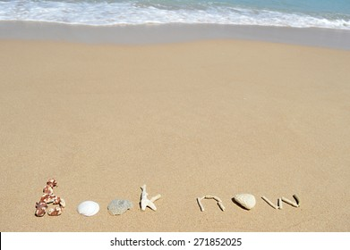 Call to book a beach holiday or tour written with corals in the sand at the beach