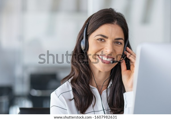 Call center agent with headset working on support hotline in modern office with copy space. Portrait of mature positive agent in conversation with customer over headset looking at camera.