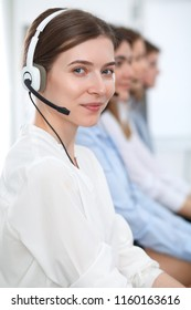 Call center. Beautiful cheerful smiling operator consulting clients with headset. Business concept of customer service