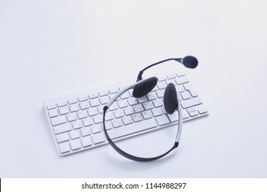 Call center and customer service help desk. VOIP headset on laptop computer keyboard
