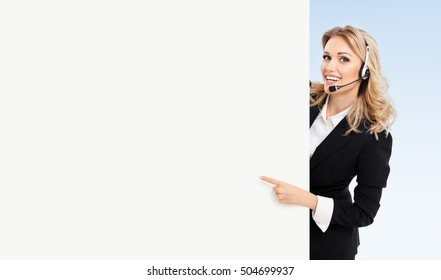 Call center. Customer support service phone operator in headset showing signboard with copyspace area for text or advertise slogan, blue background. Caucasian blond model in business success concept.