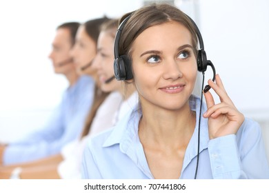 Call center operator in headset while consulting client. Telemarketing or phone sales. Customer service and business concept
