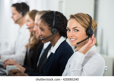 Call Center Operators In A Row Working On Computers In Office