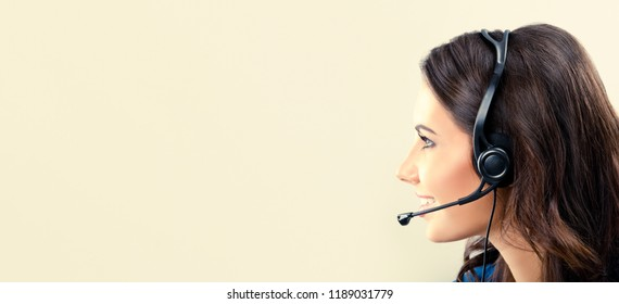 Call center. Portrait of female support phone operator in headset, with empty copyspace place for advertising slogan or text message. Brunette model in help service and client consulting concept.