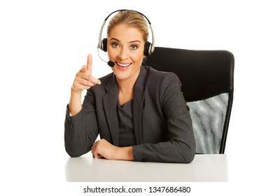 Call center woman with headphones sitting at the desk, on white background.