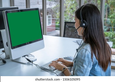 Call center woman sitting in customer service office in front of the computer, green screen with clipping path