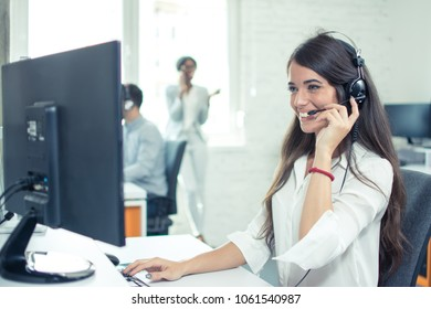 Call center worker with headset working on computer. Smiling customer support operator at work.