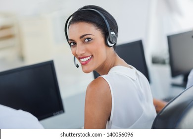 Call centre agent looking over shoulder with her headset