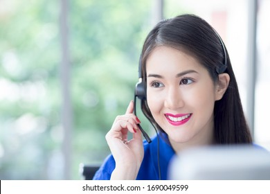 call centre. smiling friendly Beautiful face asian woman blue shirt operator working with headset look sideway front of computer screen. Technical support Customer Service agent in an startup office.