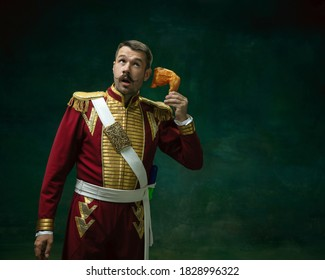 Call chicken. Young man in suit as Nicholas II isolated on dark green background. Retro style, comparison of eras concept. Beautiful male model like historical character, monarch, old-fashioned.