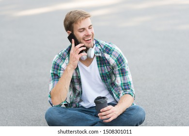 Call friend. Guy carefree student enjoy coffee outdoors. Life balance. Wellbeing and health. Having coffee break. Man sit on ground while drinking coffee. Relax and recharge. Have fun during break.