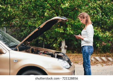 Call the help of an auto repair service by phone. The girl is waiting for the tow truck. The girl is upset by the car breakdown.