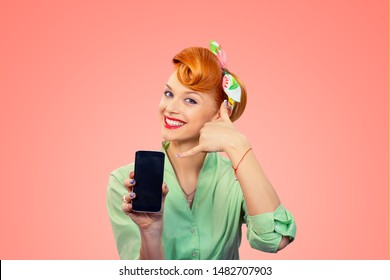 Call me. Closeup redhead young woman pretty smiling pinup girl green button shirt showing phone screen giving call me sign hands gesture looking at you camera, retro vintage 50's hairstyle on pink