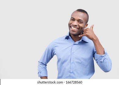Call me! Handsome young African man showing a call me sign and smiling while standing isolated on grey background