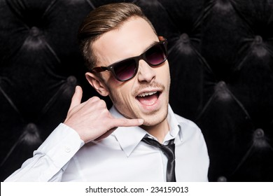 Call me! Handsome young man in shirt and tie gesturing telephone near face while standing against black background
