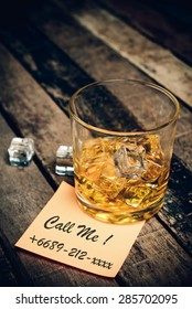 call me with label on paper note. Glass of scotch whiskey