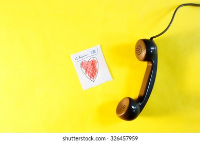 call me note and handset on a yellow background