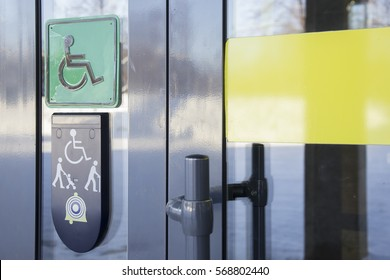 Call on glass front door of building and plaque with image of disabled person in wheelchair and people with walking stick