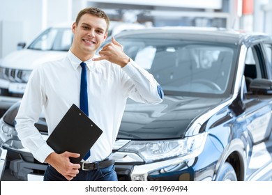 Call to preorder. Handsome smiling car dealer holding his clipboard showing call me gesture smiling cheerfully to the camera car dealership on the background