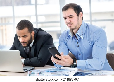Call Waiting. Two confident businessman sitting at the negotiating table in the office and holding a cell phone. Business people dressed in formal wear