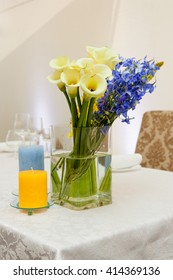 calla lily and blue flowers in tall glass tube